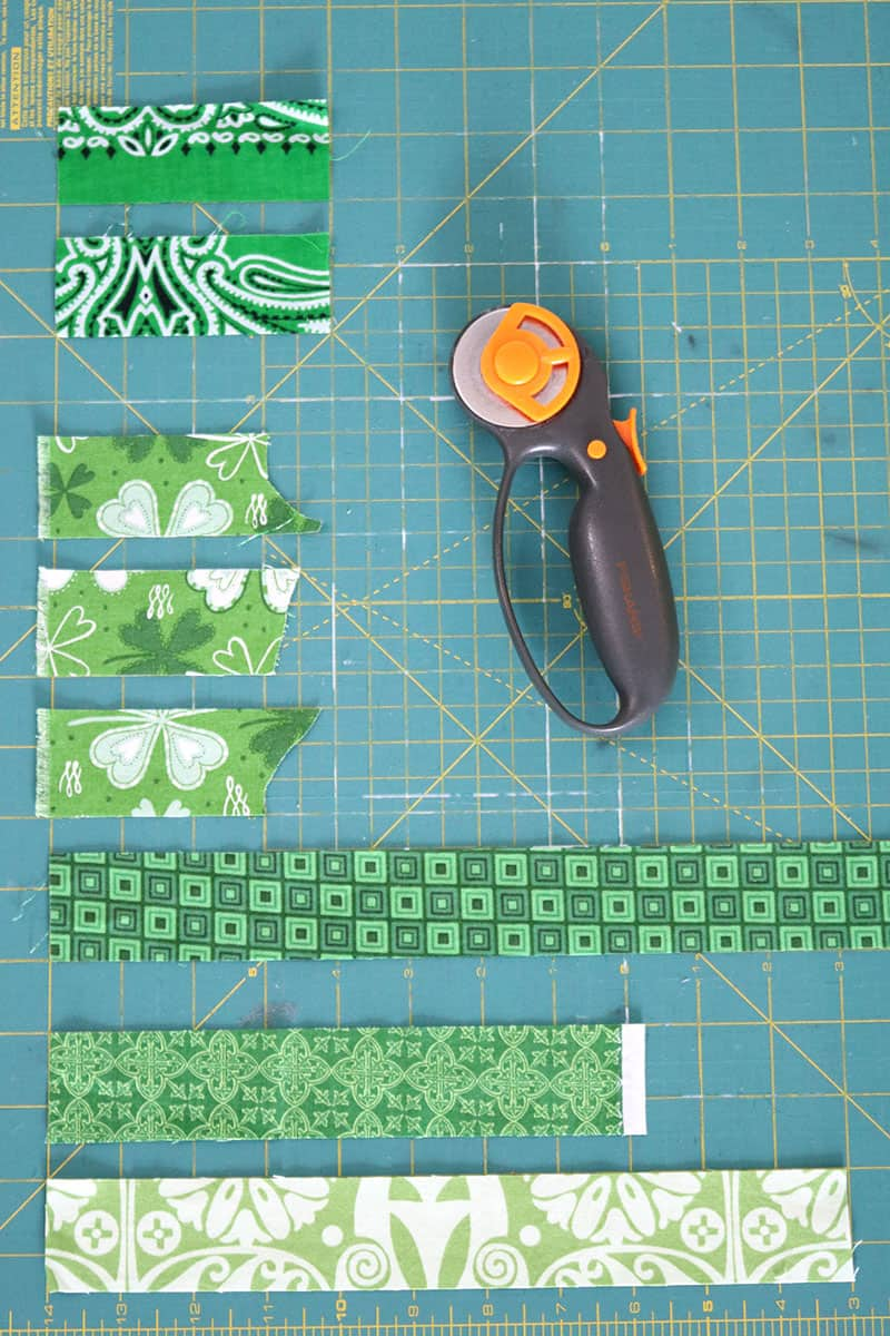 cutting green fabric with rotary cutter and mat