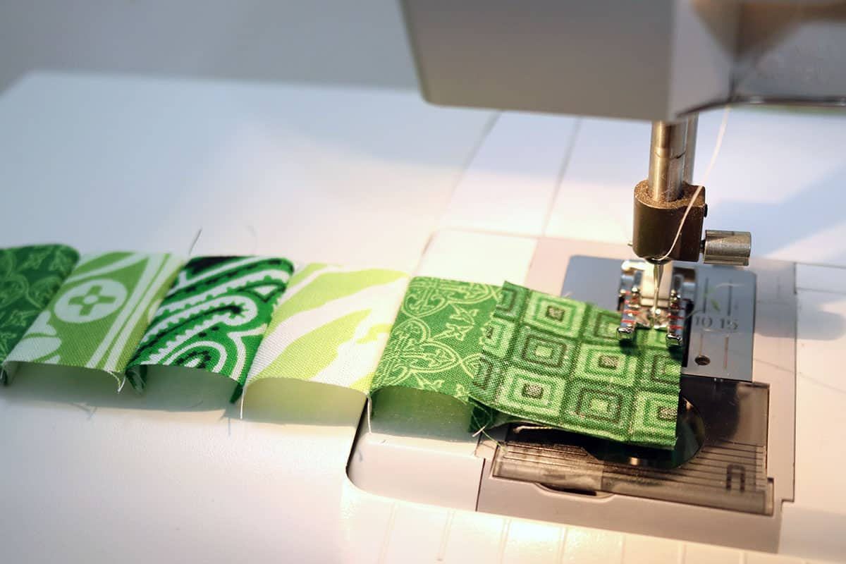 sewing machine sewing green squares together