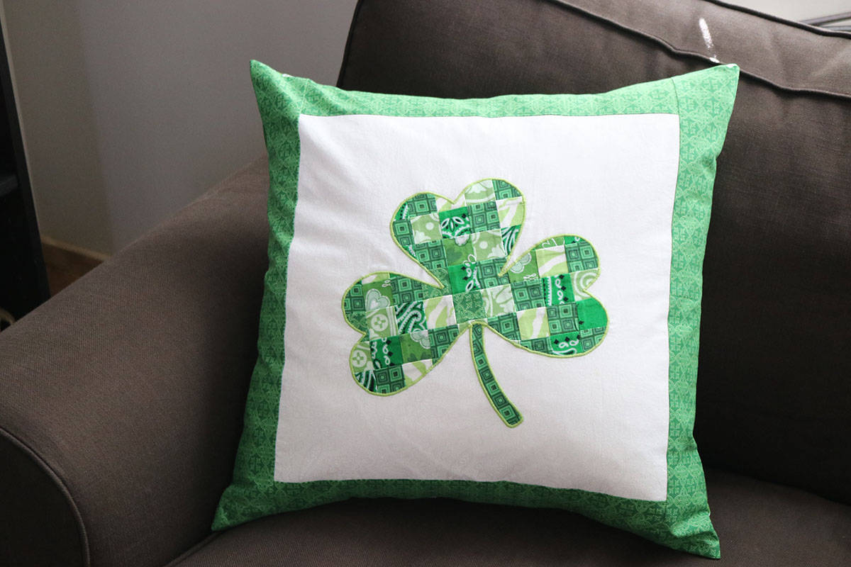 green and white shamrock applique pillow on brown couch