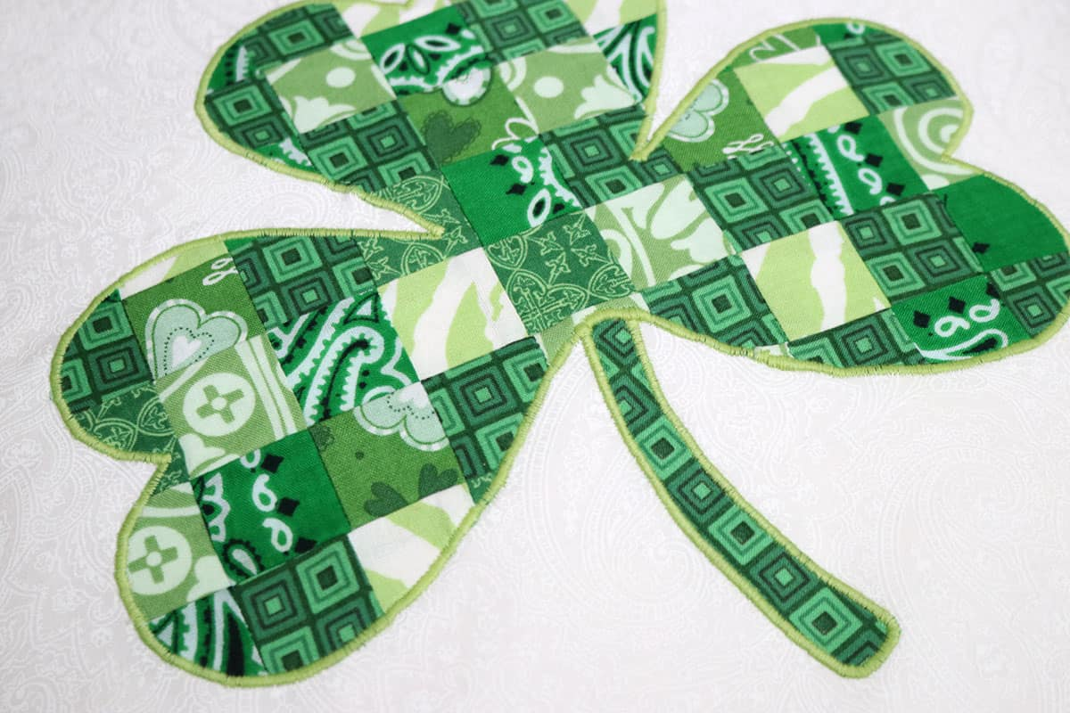 green pieced shamrock appliqued and embroidery stitched to white fabric