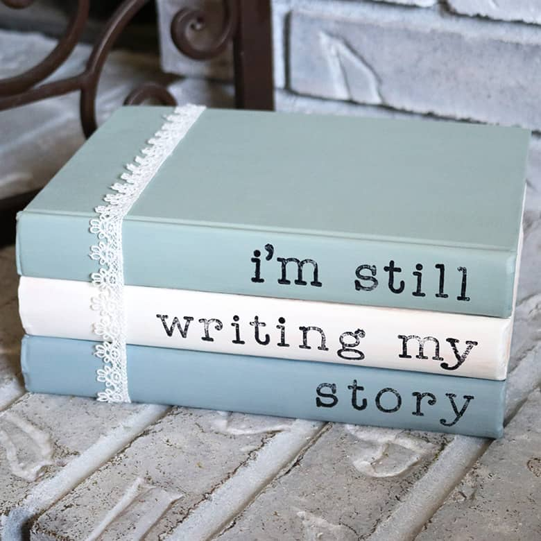 Painted books with sayings are a super easy addition to your home decor! This DIY with chalk paint and acrylic stamps is a thrifty way to use old books. Display them on shelves, use for a wedding, or lay them on a coffee table. Learn how to make them with this tutorial!