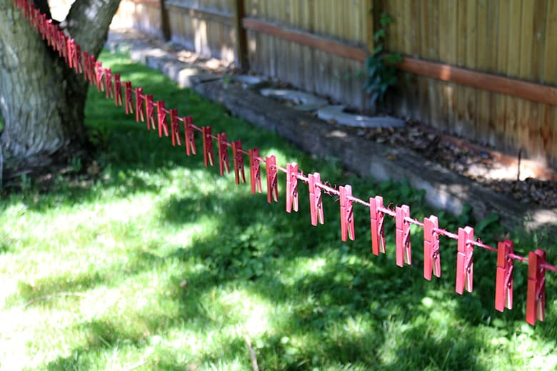 painting clothespins on a line for a clothespin wreath