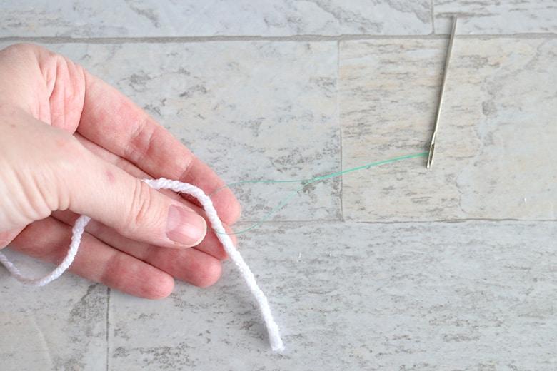 threading yarn onto a needle for a DIY ghost garland