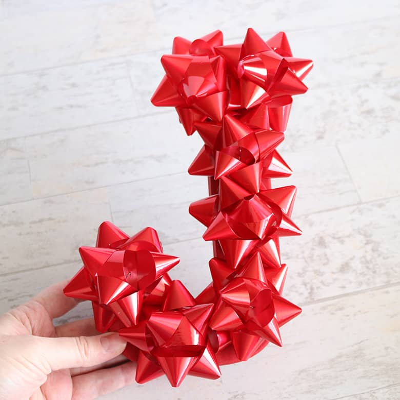 """Christmas letters made with stick-on Christmas bows to spell """"JOY"""""""